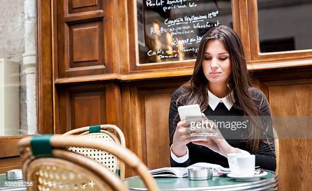 女性彼女のチェック、ソーシャルメディアでリラックスしながら、カフェテリア - スポーツ チェックする ストックフォトと画像