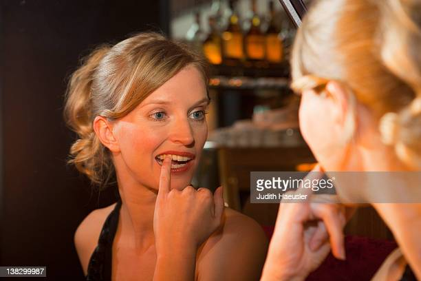 Woman checking her teeth in mirror