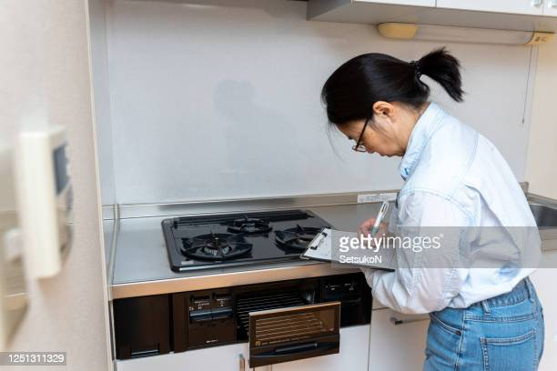 woman checking house equipment - burner stove top stock pictures, royalty-free photos & images