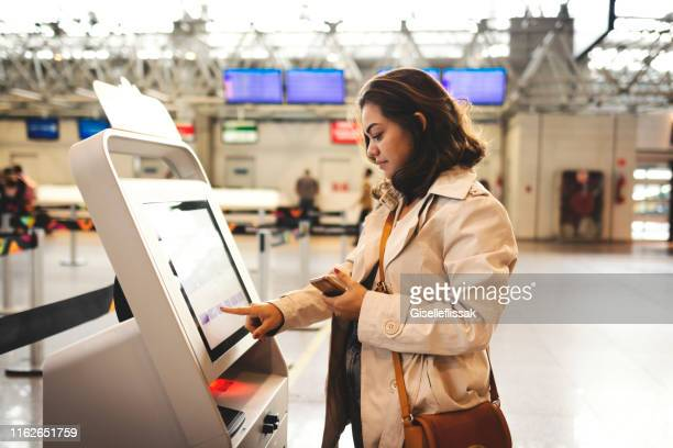 woman checking in at the airport - touch screen stock pictures, royalty-free photos & images