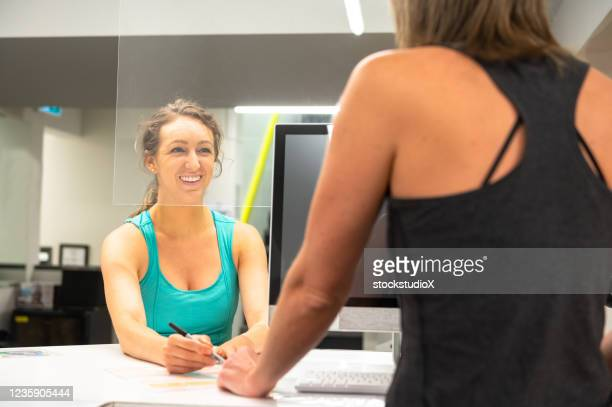 woman checking in behind plexi galss - opening event stock pictures, royalty-free photos & images