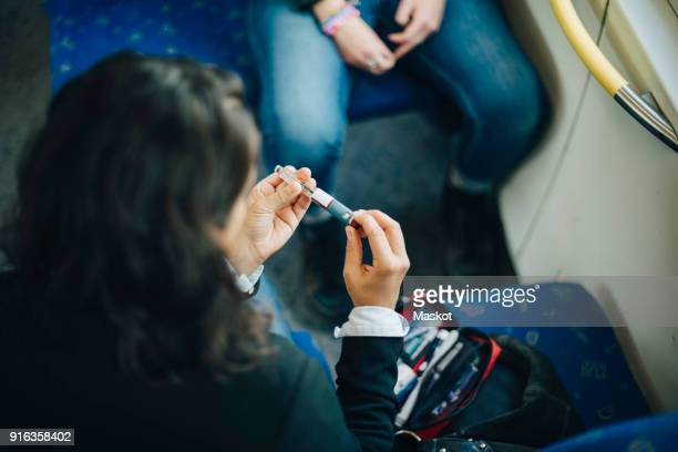 Woman checking injection pen while sitting in train