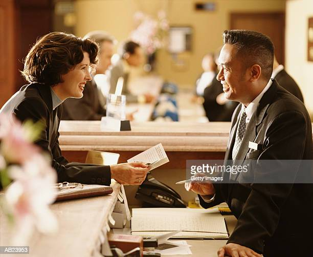 Woman checking into hotel at front desk