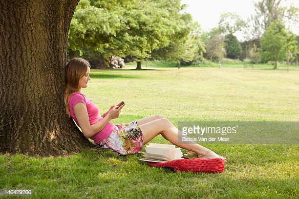 Woman checking messages, sitting under tree.