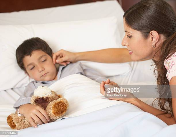 Woman checking on young boy sleeping in hospital bed with teddy bear