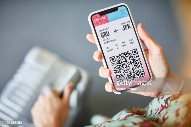 woman checking online airplane ticket on cellphone - ticket stock pictures, royalty-free photos & images