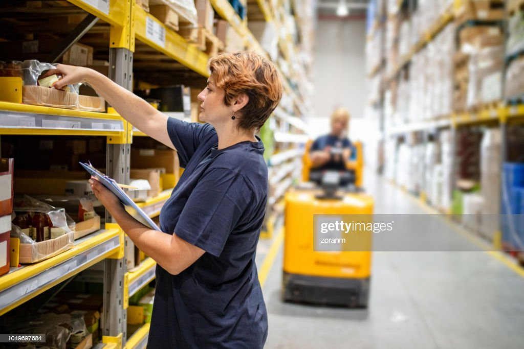 Woman checking packages on warehouse racks : Stock Photo