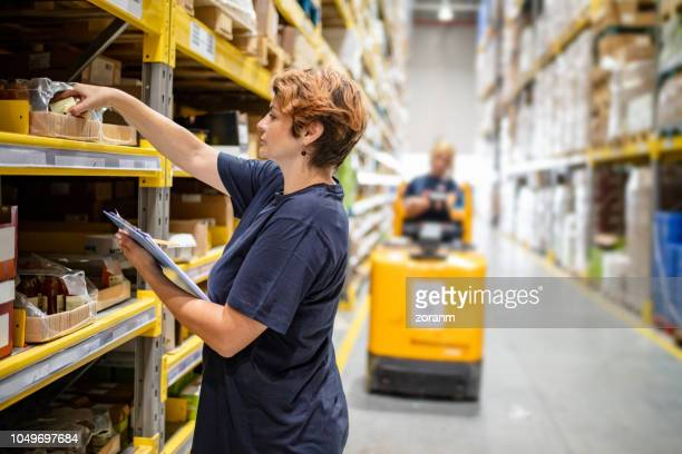 woman checking packages on warehouse racks - 40 44 jaar stock pictures, royalty-free photos & images