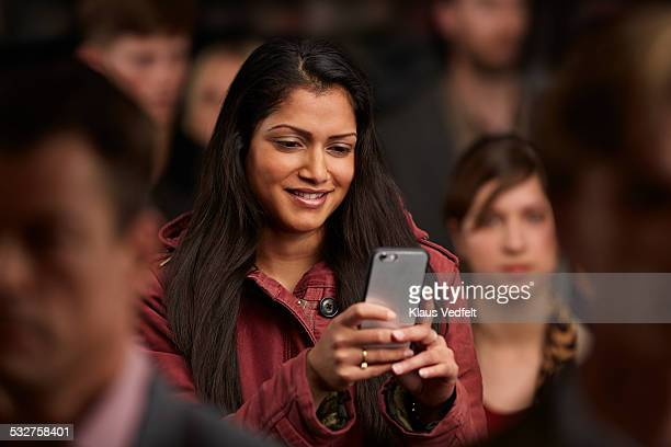 Woman checking phone, standing in crowd