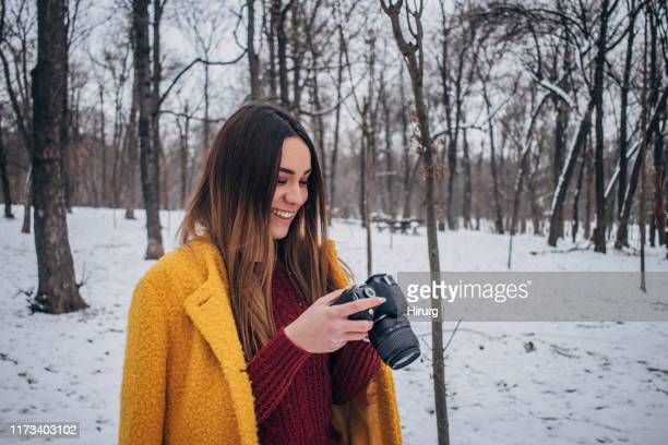 woman checking photos on camera - digital camera stock pictures, royalty-free photos & images
