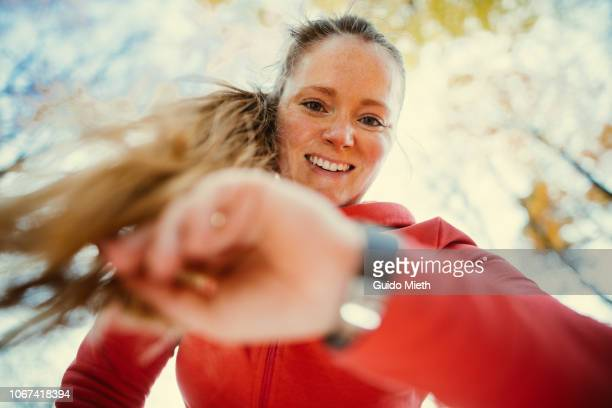woman checking pulse after jogging. - fitness or vitality or sport and women stock photos and pictures