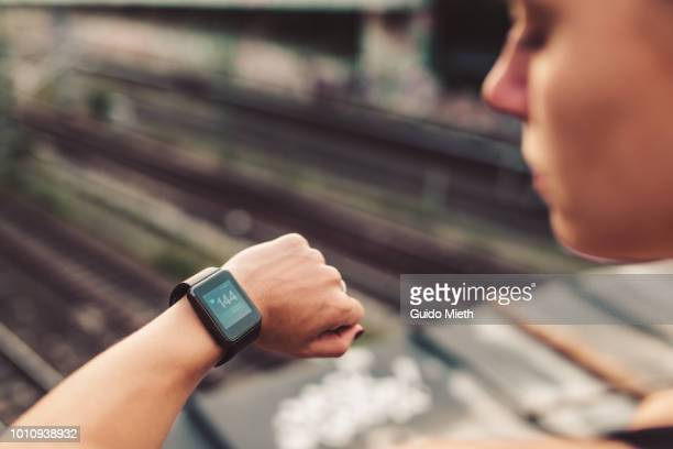 woman checking pulse after running. - smart watch stock pictures, royalty-free photos & images