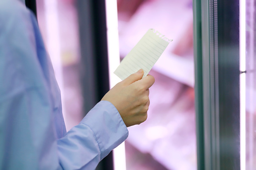 Woman checking  shopping list at refrigerated section in supermarket - gettyimageskorea