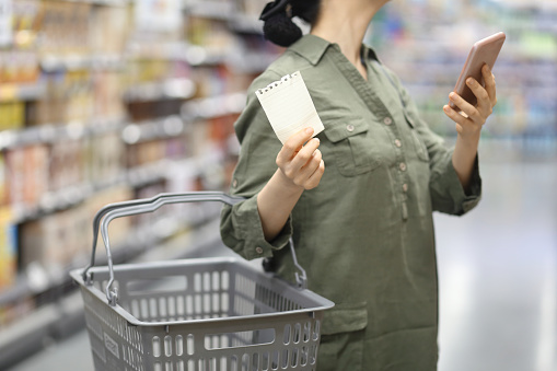 woman checking shopping list in supermarket - gettyimageskorea