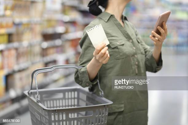 woman checking shopping list in supermarket