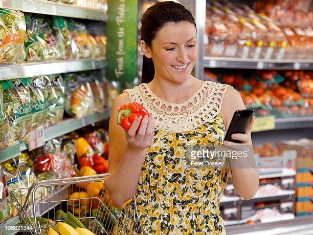 Woman checking shopping list on mobil phone