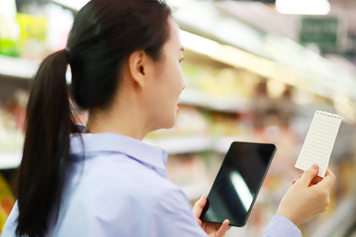 Woman checking shopping list with digital tablet in supermarket - gettyimageskorea