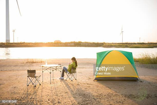Woman checking smartphone on camping chair.
