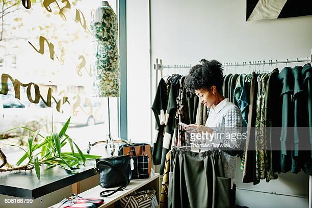 woman checking smartphone while shopping - boutique stock photos and pictures