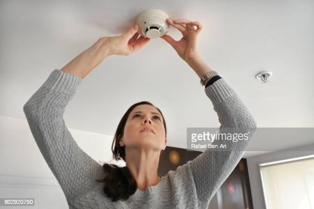 woman checking smoke detector - rafael ben ari ストックフォトと画像