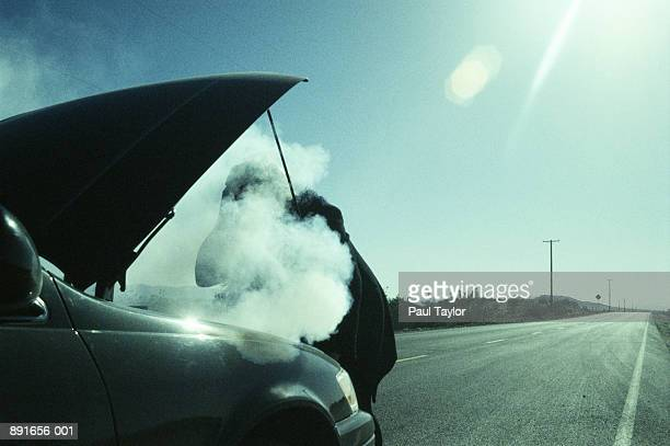 woman checking smoking hood of car - vehicle breakdown stock pictures, royalty-free photos & images