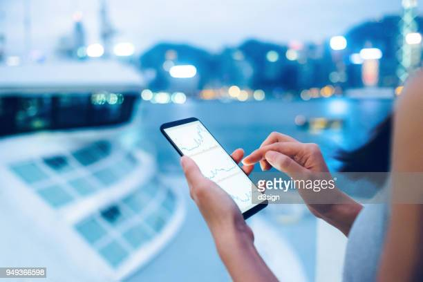 woman checking stocks and shares data with smartphone in city - finanza foto e immagini stock