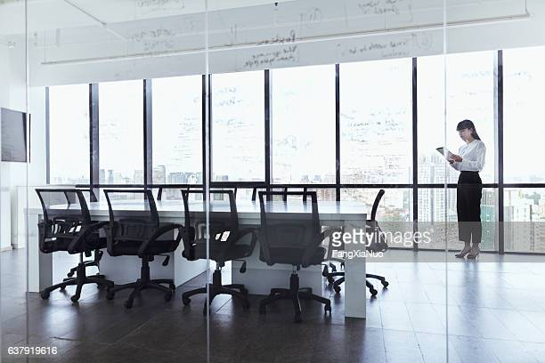 Woman checking tablet computer in conference room