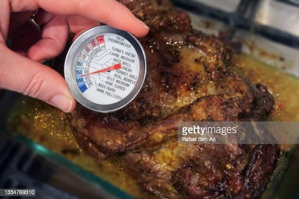 woman checking temperature of a roasted lamb from an oven - rafael ben ari photos et images de collection