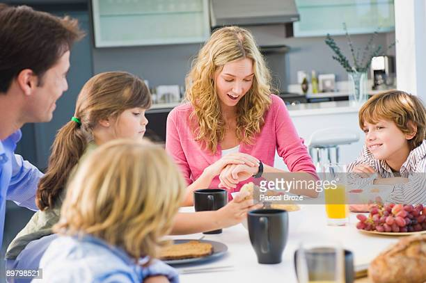Woman checking the time and having breakfast with her family