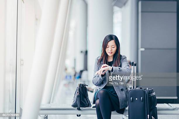 woman checking the time while waiting at airport - yiu yu hoi stock pictures, royalty-free photos & images