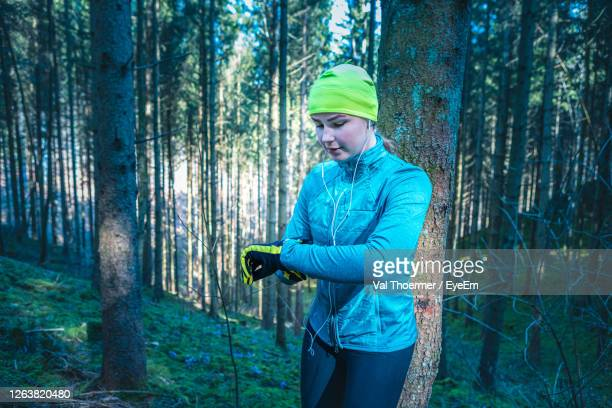woman checking time while standing in forest - val thoermer stock-fotos und bilder