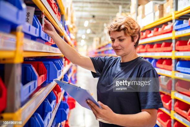 woman checking trays on shelves in warehouse - industrial storage bins stock pictures, royalty-free photos & images