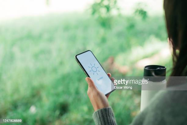 woman checking weather forecast on smartphone display - telephone stock pictures, royalty-free photos & images