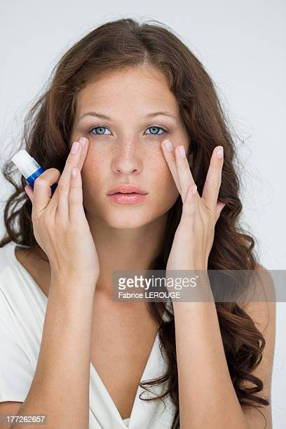 woman checking wrinkles on her face - faltenreduktion stock-fotos und bilder