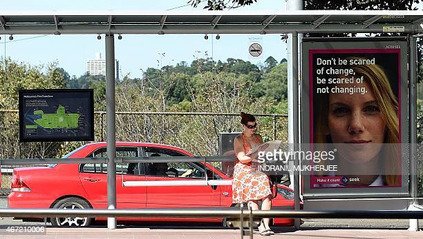 A woman checks a map as she waits at a tram stop in Melbourne on March 22 2015 AFP PHOTO / INDRANIL MUKHERJEE