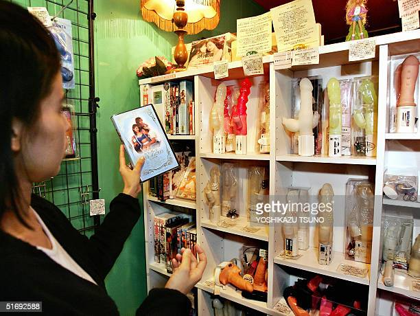 A woman checks a pornographic video tape and dildos displayed at a woman only sex shop in Tokyo 03 November 2004 Craving sex after repeated rejection...