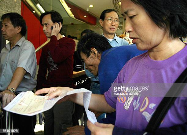 A woman checks an application form for Link Real Estate Investment Trust before dropping it into the collection box during the last day of the retail...
