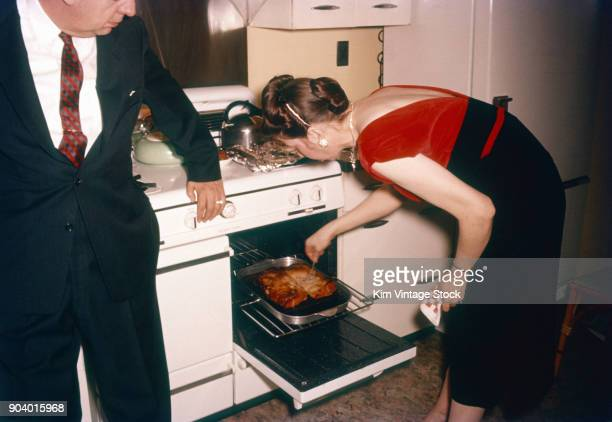 woman checks food oven during party