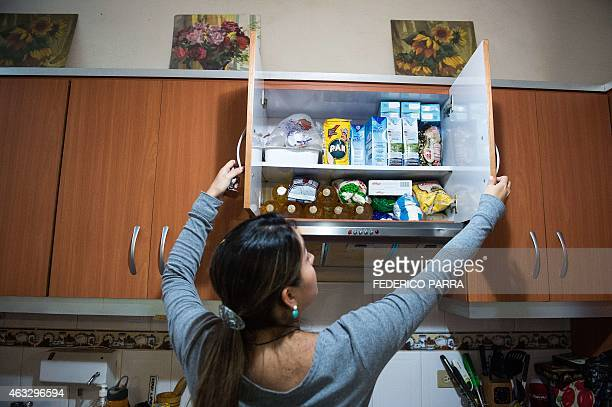 A woman checks food stocks in her kitchen cupboard in Caracas on February 2 2015 The shortage of food and different products in Venezuela has...