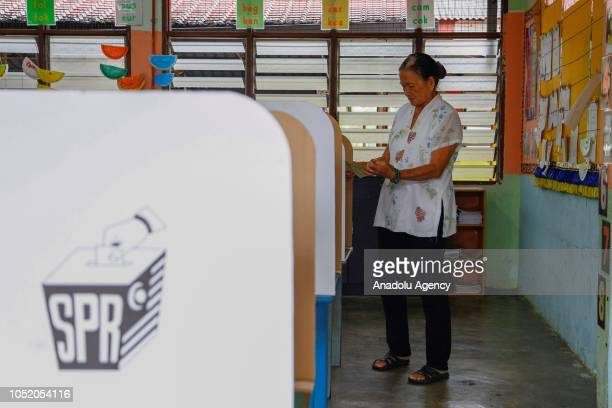 A woman checks her ballot at a polling station during the byelection in Port Dickson on October 13 2018 The Port Dickson seat was vacated to enable...