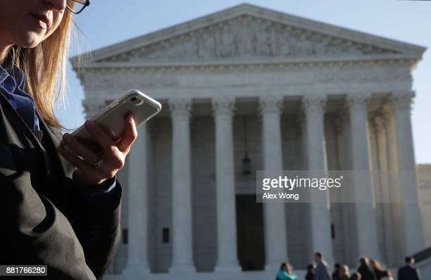 A woman checks her cell phone as she waits in line to enter the US Supreme Court to view a hearing November 29 2017 in Washington DC The Supreme...