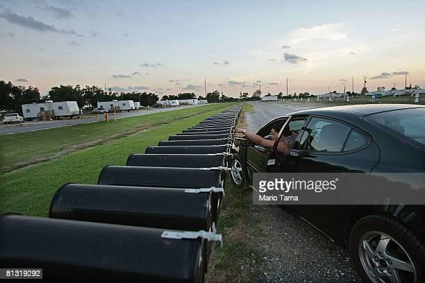 A woman checks her mailbox in the FEMA Diamond trailer park May 31 2008 in Port Sulphur Louisiana FEMA federal trailer parks that house many...