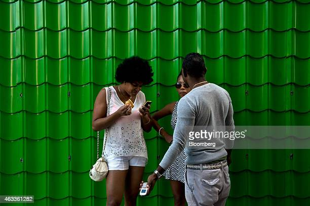 A woman checks her mobile phone during a conversation with friends in Havana Cuba on Saturday Jan 31 2015 US companies will be permitted to export to...