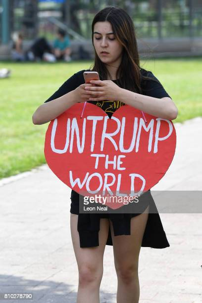 A woman checks her mobile phone wearing an antiTrump sign as protesters gather to participate in an antiG20 march on July 7 2017 in Hamburg Germany...