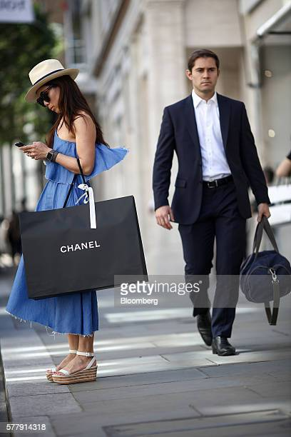 A woman checks her mobile phone whilst holding a Chanel SA luxury goods branded shopping bag on New Bond Street in London UK on Tuesday July 19 2016...