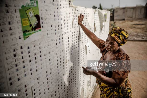 TOPSHOT A woman checks her name in a voting list without knowing that the general elections was postponed at a polling station in Yola on February 16...