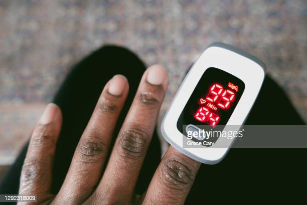 woman checks her oxygen saturation level and heart rate - pulse oximeter stock pictures, royalty-free photos & images