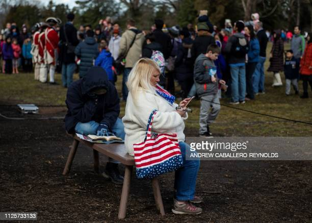 A woman checks her phone as reenactors play music as part of Presidents day events at George Washingtons' Mount Vernon estate in Mt Vernon Virginia...