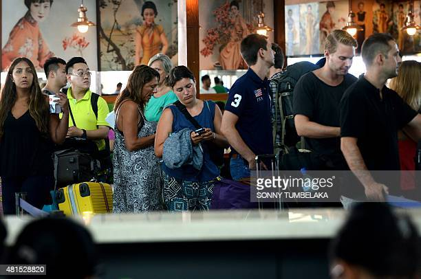 A woman checks her phone as she queues with other passengers for information about delayed flights at the international departure area of Bali's...