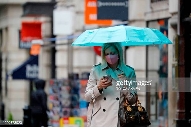 Woman checks her phone as she shelters under an umbrella in the rain on Oxford Street in London on June 18 as some non-essential retailers reopen...